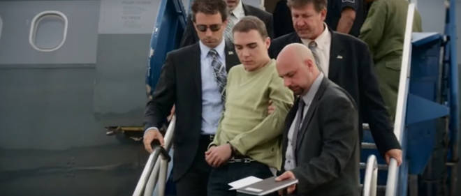 Luka Magnotta gets off a plane escorted by law enforcement