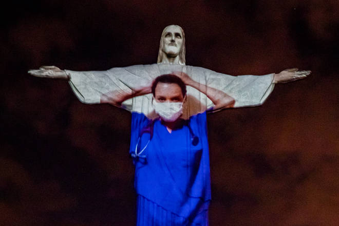 Christ the Redeemer lit up with images of frontline workers projected.