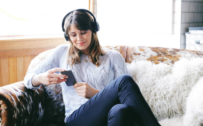 Stock photo of a woman looking at her phone wearing headphones