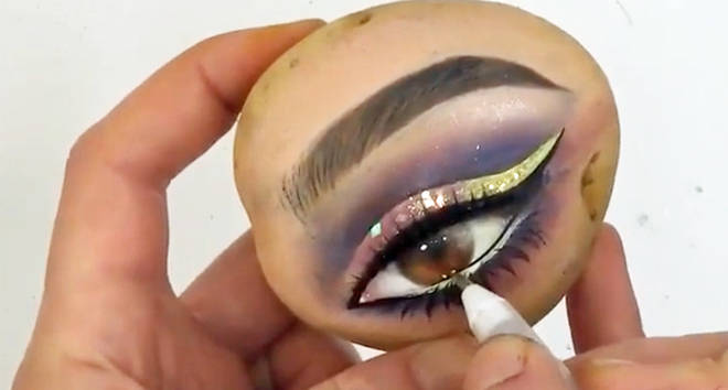 Makeup artist putting makeup on a potato.