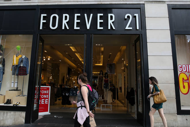 Shoppers walk past a branch of Forever 21 store in central...